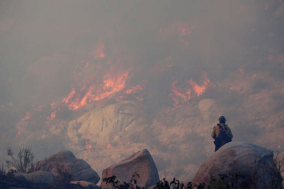 A firefighter watches a backfire burn while battling a wildfire, Thursday, Aug. 8, 2013, in Banning, Calif. About 1,500 people have fled and three are injured as the wildfire in the Southern California mountains quickly spreads. Several small communities have evacuated. (AP Photo/Jae C. Hong) / AP
