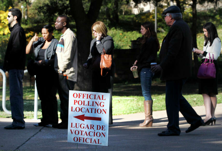 A sign guides voters to a polling location as they line up to cast their votes Tuesday, Nov. 6, 2012, in Dallas. After a grinding presidential campaign, Americans head into polling places across the country. (AP Photo/Tony Gutierrez) / AP