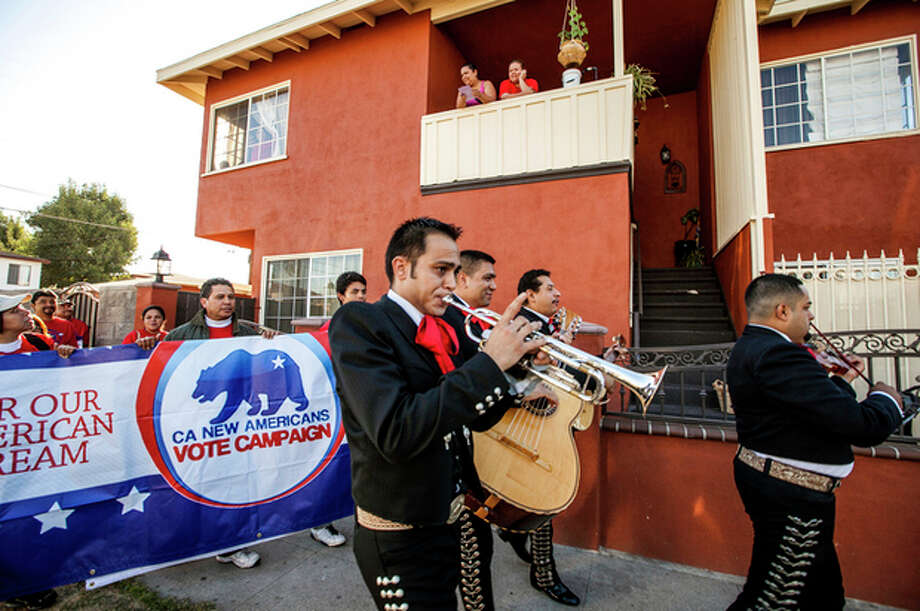 "Members of the mariachi band ""Gallos de Jalisco"" play to remind California citizens to get out and cast their vote on Tuesday, Nov. 6, 2012 in the Sun Valley district of Los Angeles. Latinos now number about 53 million in the U.S., about 17 percent of the population, with some 24 million eligible to vote. (AP Photo/Damian Dovarganes) / AP"