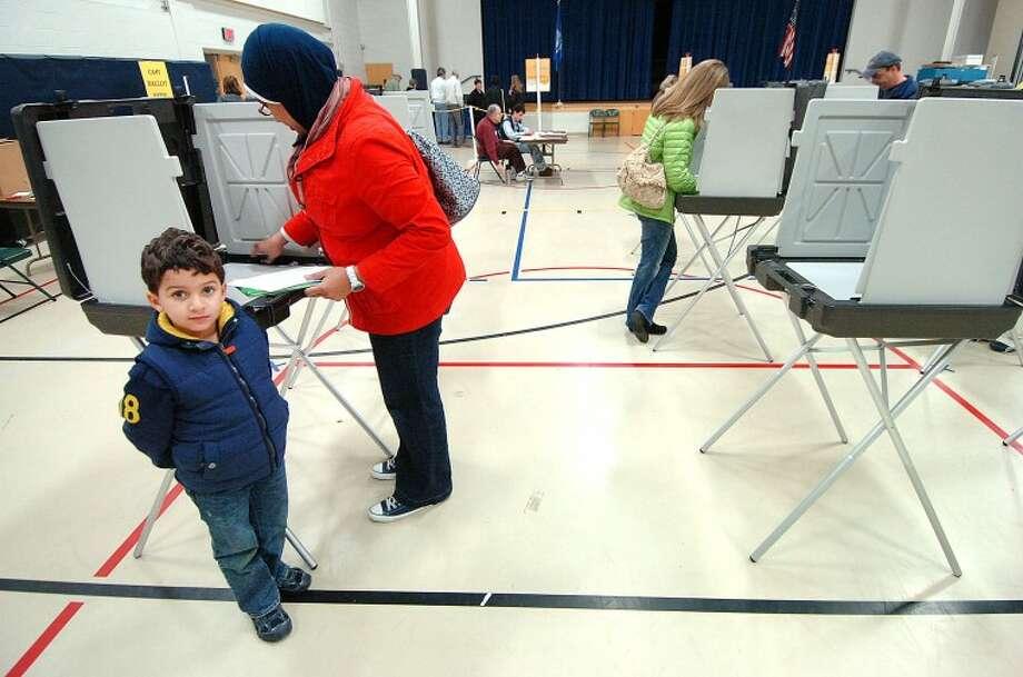 Hour Photo Alex von Kleydorff; 4 yr old Ali Mubarek waits while mom Nisreen casts her vote at Wilton's District 2 on election day.