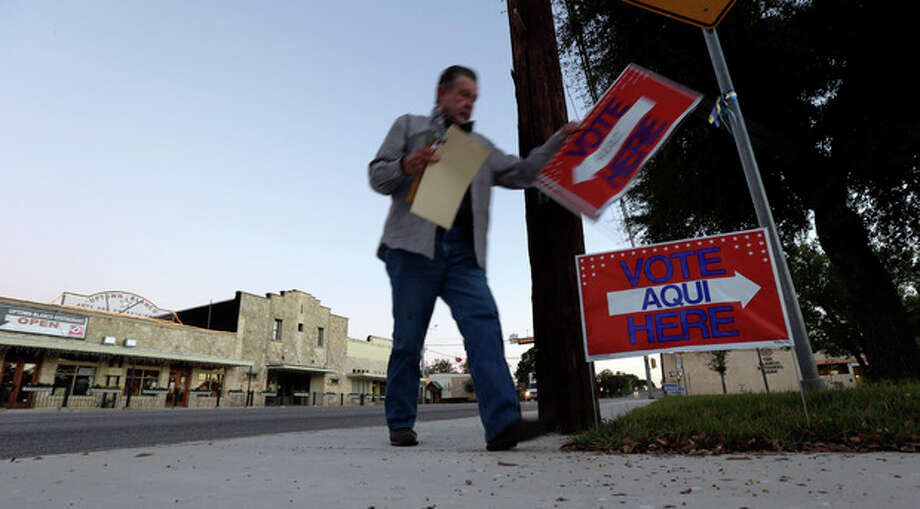Alternate election clerk Van Downing posts signs prior to the polls opening Tuesday, Nov. 6, 2012, on the downtown square in Blanco, Texas. (AP Photo/Eric Gay) / AP