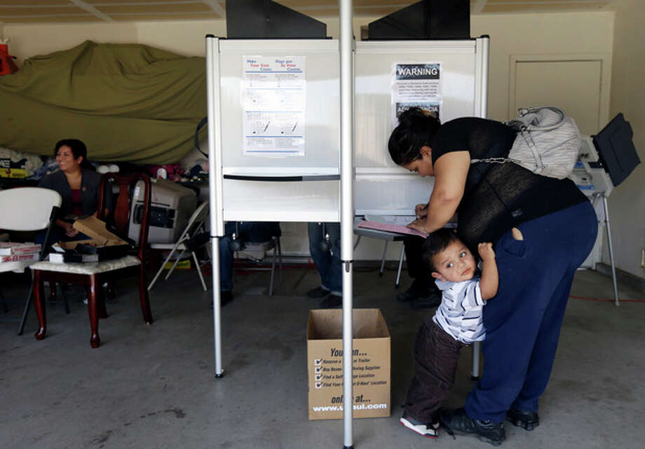 Yesenia Perez marks her ballot as her 1-year-old Eduardo Sanchez clings to her in the Weston Ranch area of Stockton, Calif. on Tuesday, Nov. 6, 2012. The neighborhood was heavily affected by foreclosures in the past few years. Perez, 34, a mother of five who works at a local fruit-packing house, has had her share of hard times. After both she and her husband had their work hours cut amid the sputtering economy, they lost their home to foreclosure three years ago. Yet on Tuesday, she felt compelled to do something she had never done before: vote. (AP Photo/Marcio Jose Sanchez) / AP