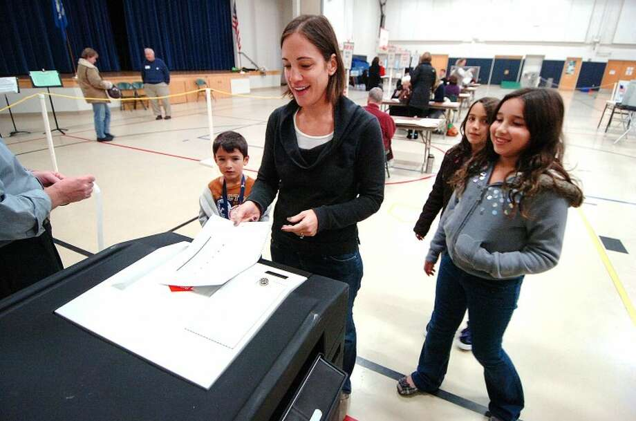 Hour Photo Alex von Kleydorff; Jessica Kaplan feeds her ballot into the voting machine with her kids Ava, Gracie and Levi at Cider Mill School in Wilton