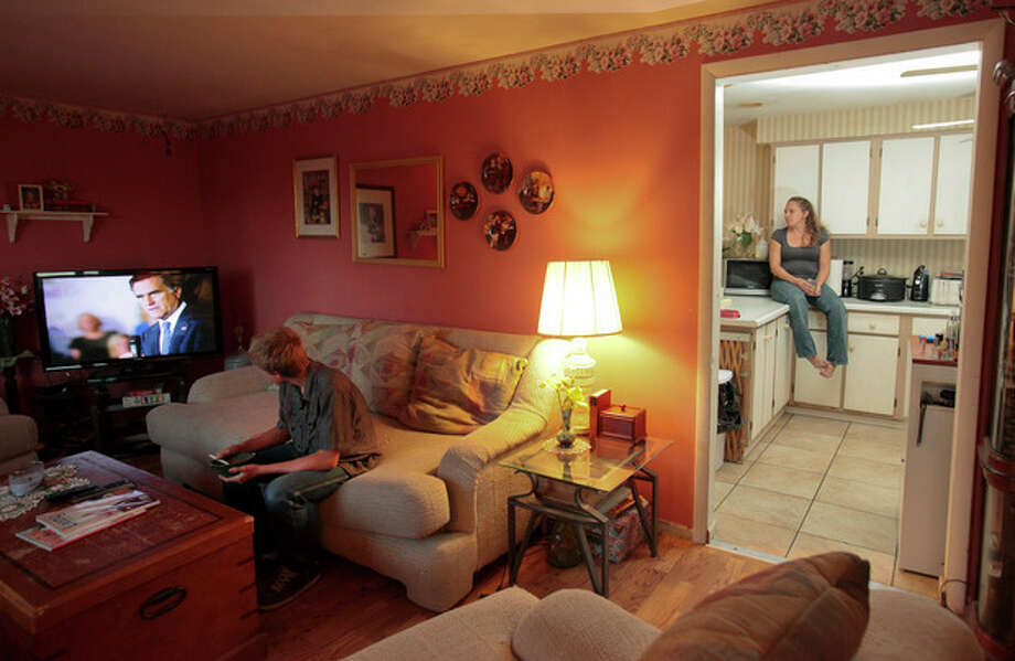 Amber Tuffield, 44, right, a single mother of three, sits in her kitchen while her son Dallas, 13, watches a political advertisement on television at their home on Election Day, in Lakewood, Colo., Tuesday Nov. 6, 2012. (AP Photo/Barry Gutierrez) / FR170088 AP