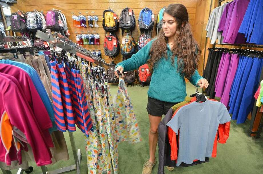 Sales Person Julia Nachemson organizes some of the clothes in the children's apparel department at Outdoor Sports Center on Rourt 7 in Wilton.