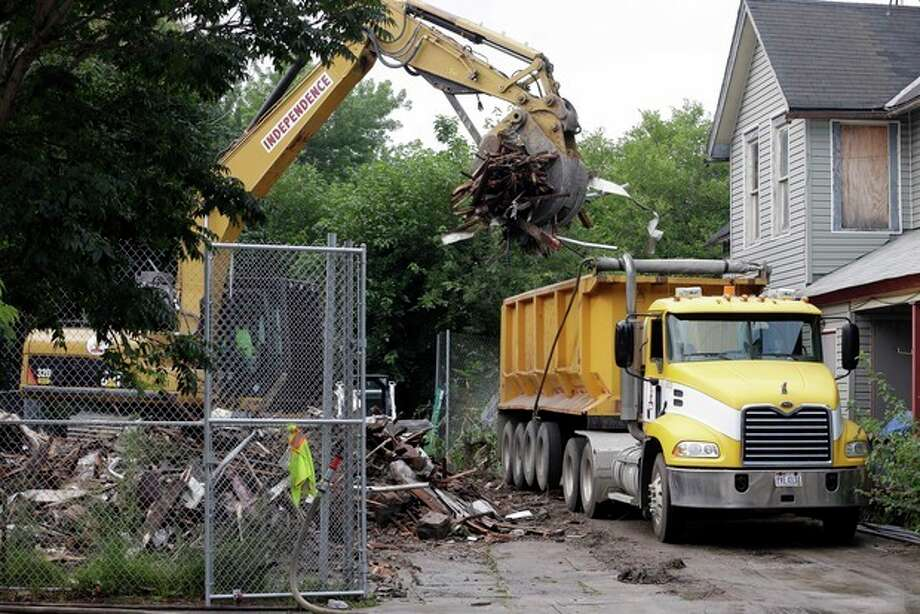 "Debris is loaded onto a truck at a house where three women were held captive and raped for more than a decade, Wednesday, Aug. 7, 2013, in Cleveland. Authorities want to make sure the rubble isn't sold online as ""murderabilia,"" though no one died there. The house was torn down as part of a deal that spared Ariel Castro a possible death sentence. He was sentenced last week to life in prison plus 1,000 years. He apologized but blamed his addiction to pornography. (AP Photo/Tony Dejak) / AP"