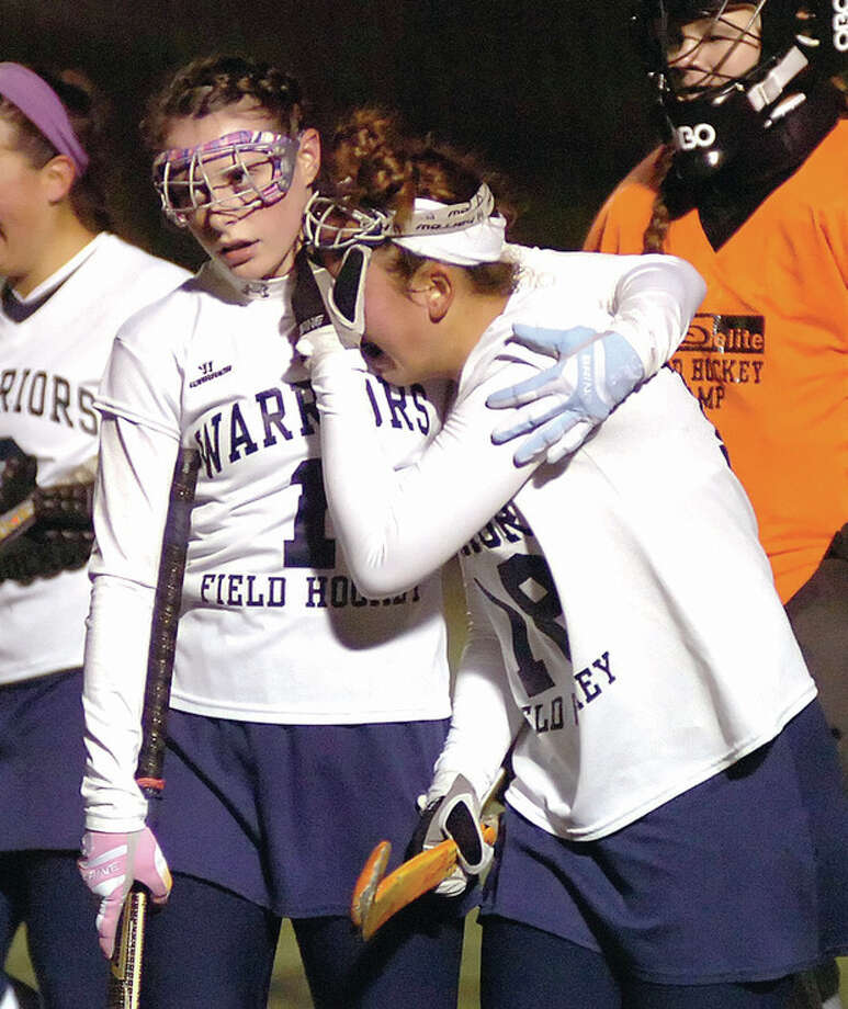 Hour photo/John NashA crestfallen Madison Hendry, right, is comforted by Wilton teammate Megan Cunningham as the two walk off the field at the after Greenwich Cardinals topped the Warriors 2-1 in overtime in one of two FCIAC co-championship games at Dunning Field in New Canaan.