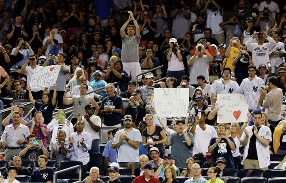 Fans cheer and hold signs for New York Yankees' Alex Rodriguez during his first at-bat during the first inning of a baseball game against the Detroit Tigers on Friday, Aug. 9, 2013, in New York. (AP Photo/Frank Franklin II) / AP