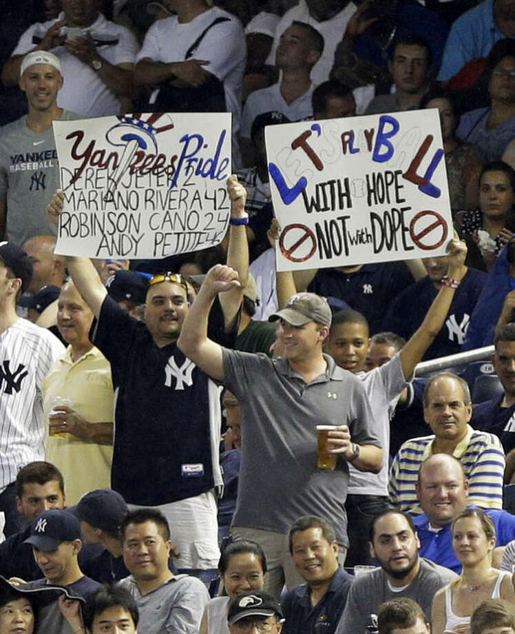Fans hold up signs during New York Yankees' Alex Rodriguez's first at-bat in the first inning of a baseball game against the Detroit Tigers on Friday, Aug. 9, 2013, in New York. (AP Photo/Frank Franklin II)