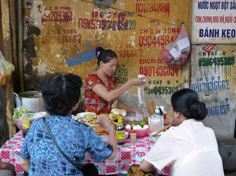 FILE - This April 14, 2008 file photo shows a woman cooking noodle for her customers at a stall in a street in Old Quarter district in Hanoi, Vietnam. The 36 ancient streets that make up Hanoi's Old Quarter are a maze of madness filled with treasures. (AP Photo/Chitose Suzuki, file) / AP