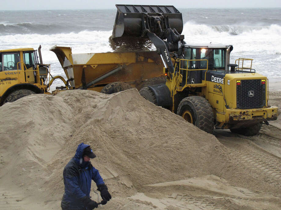 AP photoAs a reporter from The Weather Channel gets set to do a broadcast on the nor'easter hitting Point Pleasant Beach N.J. , on Wednesday, workers use heavy equipment to hurriedly push piles of sand back onto the beach that was damaged last week by Superstorm Sandy. / AP