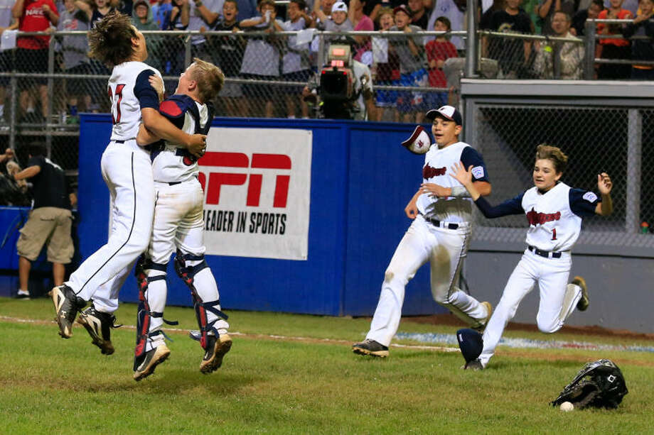 Westport's Pitcher Chad Knight leaps into the arms of Catcher Matt Stone as Matt Brown and Christopher Drbal run onto the field after Westport's 1-0 victory over Lincoln, R.I. in the Little League Baseball Eastern Regional State Championships on Saturday night at Giamatti Little League Field in Bristol, CT. (Hour Photo / Chris Palermo)