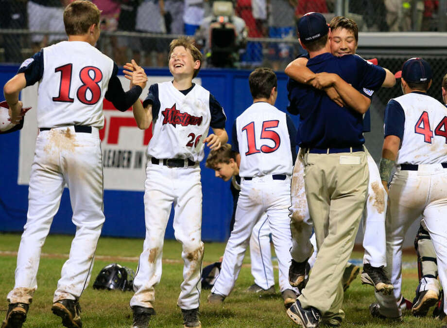 Westport's Harry Azadian (18) and Drew Rogers (26) celebrate as Chad Knight hugs Manager Tim Rogers after Westport's 1-0 victory over Lincoln, R.I. in the Little League Baseball Eastern Regional State Championships on Saturday night at Giamatti Little League Field in Bristol, CT. (Hour Photo / Chris Palermo)