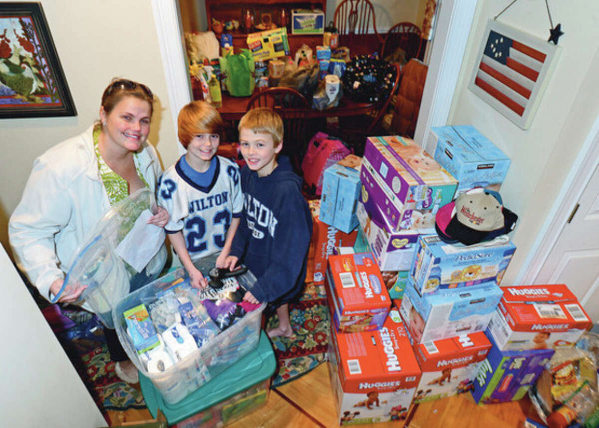 Hour photo / Erik Trautmann Wilton resident Krissy Wood with her helpers, Ryan Wood and Thomas Costello, organized a massive donation effort to aid victims of Hurricane Sandy.
