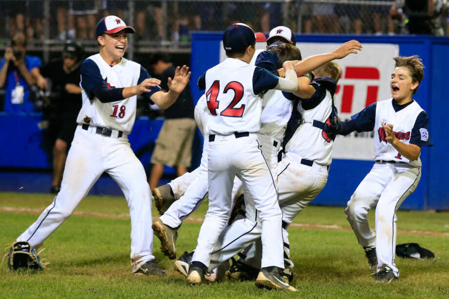 The Westport Little Leaguers celebrate after Chad Knight struck out the final batter in Westport's 1-0 victory over Lincoln, R.I. in the Little League Baseball Eastern Regional State Championships on Saturday night at Giamatti Little League Field in Bristol, CT. (Hour Photo / Chris Palermo)