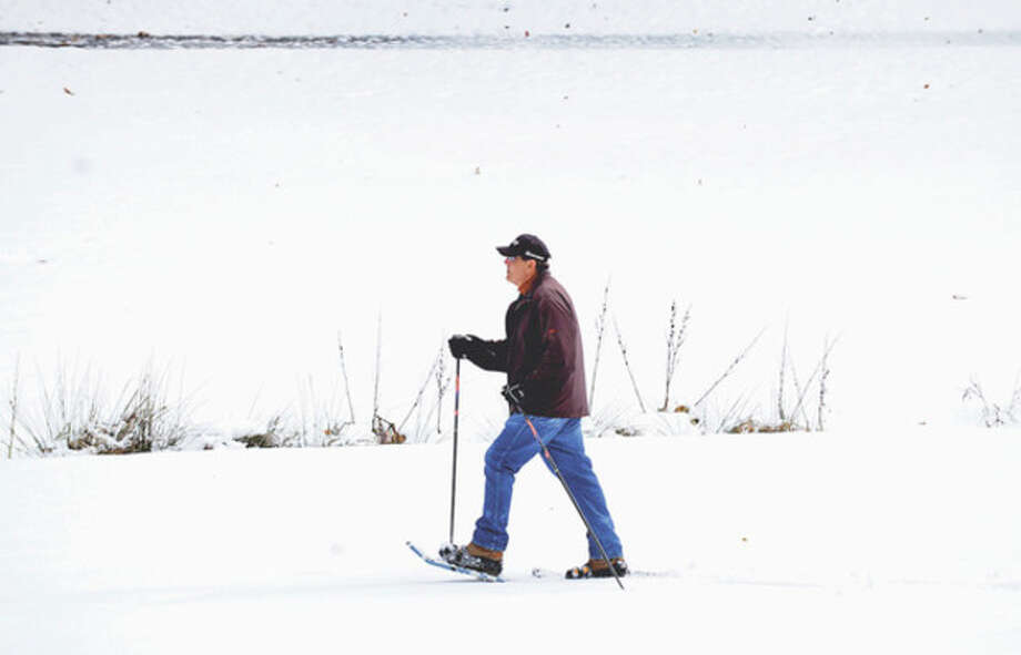 A man snow shoes through Oak Hills Golf Course following the snowfall Thursday.Hour photo / Erik Trautmann / (C)2012, The Hour Newspapers, all rights reserved