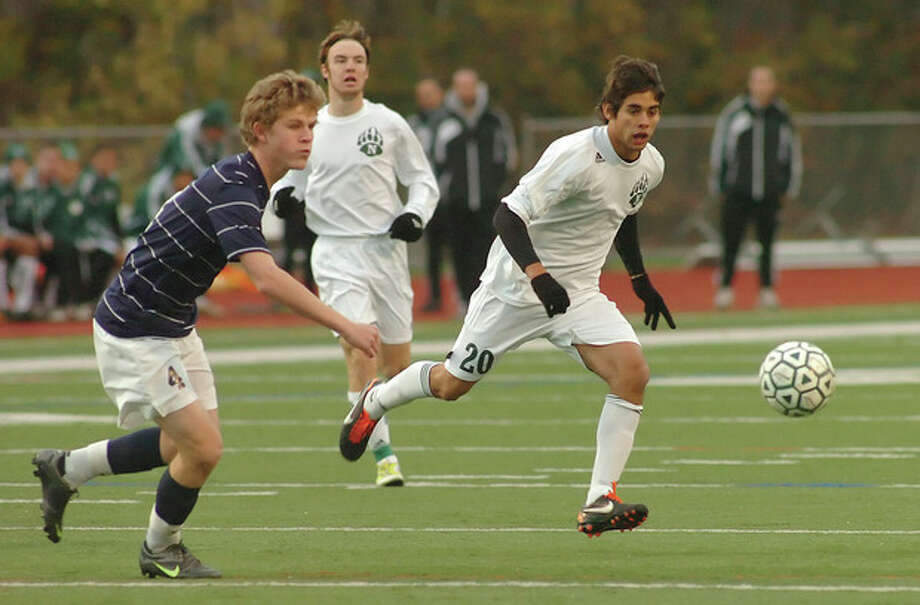 Hour photo/John NashNorwalk's Nacho Navarro, right, pursues the ball as he races past Staples' Harry Birch, left, as Norwalk's Kevin Joslyn looks on during Saturday's Class LL boys soccer second roun d game at Testa Field. The top-seeded Bears advanced with a 1-0 victory.