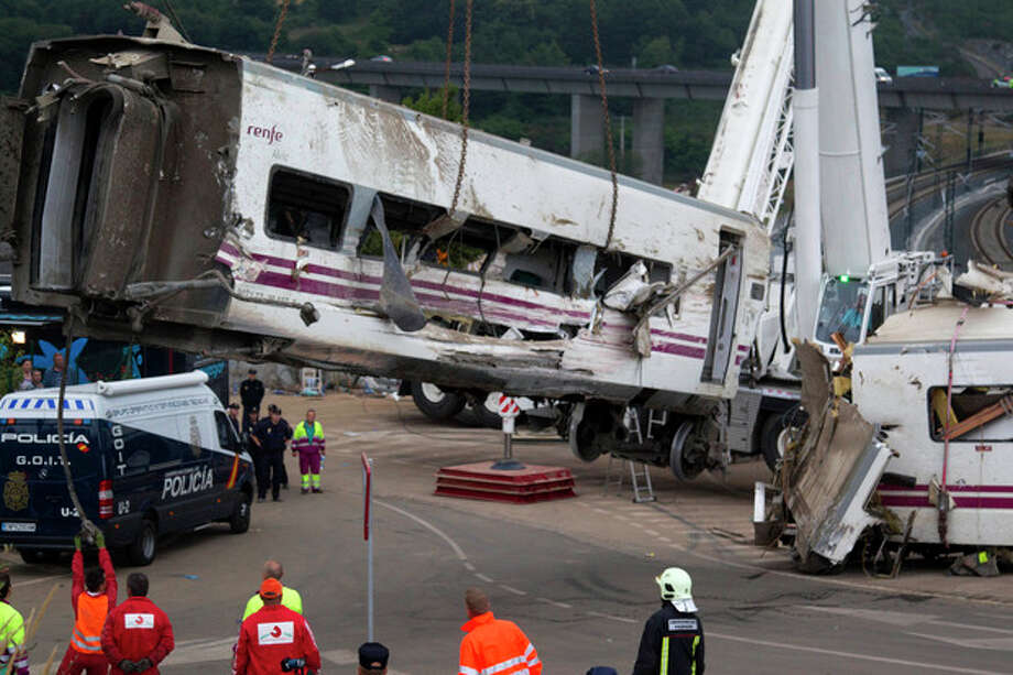 Derailed cars are removed as emergency personnel work at the site of a train accident in Santiago de Compostela, Spain on Thursday July 25, 2013. The death toll in a passenger train crash in northwestern Spain rose to more than 70 on Thursday after the train jumped the tracks on a curvy stretch just before arriving in the northwestern shrine city of Santiago de Compostela, a judicial official said. (AP Photo/Lalo Villar) / AP