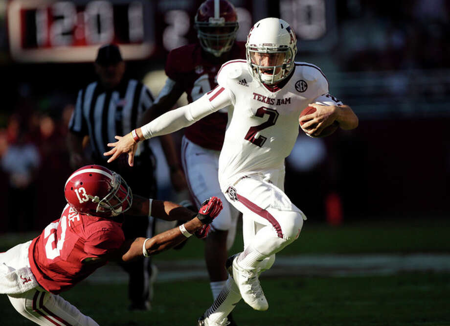 Texas A&M quarterback Johnny Manziel (2) runs through the tackle of Alabama defensive back Deion Belue (13) during the first half of an NCAA college football game at Bryant-Denny Stadium in Tuscaloosa, Ala., Saturday, Nov. 10, 2012. (AP Photo/Dave Martin) / AP