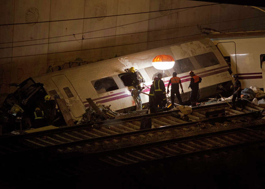 Emergency personnel conduct rescue operation at the site of a train derailed in Santiago de Compostela, Spain, on Thursday, July 25, 2013. A passenger train derailed Wednesday night on a curvy stretch of track in northwestern Spain, killing at least 40 people caught inside toppled cars and injuring at least 140 in the country's worst rail accident in decades, officials said. (AP Photo/ Lalo Villar) / AP