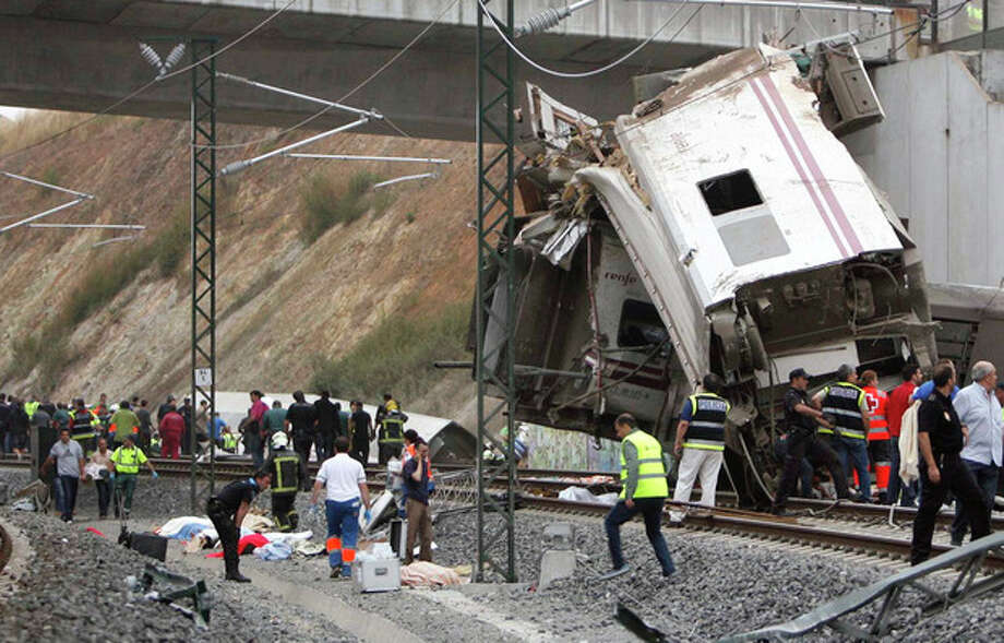 Emergency personnel respond to the scene of a train derailment in Santiago de Compostela, Spain, on Wednesday, July 24, 2013. A train derailed in northwestern Spain on Wednesday night, toppling passenger cars on their sides and leaving at least one torn open as smoke rose into the air. Dozens were feared dead, with possibly even more injured. (AP Photo/ El correo Gallego/Antonio Hernandez) / AP