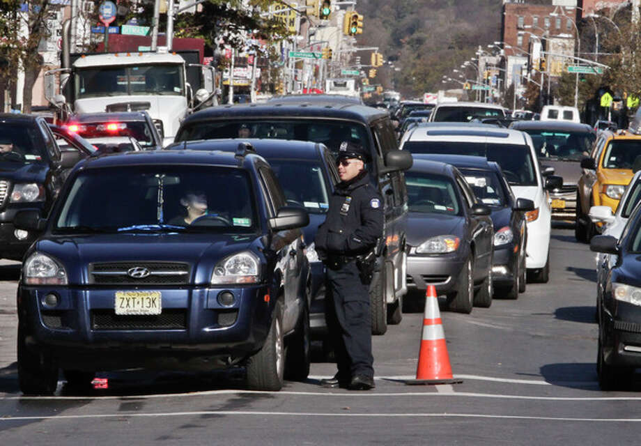 Police direct cars to gas pumps outside a gas station on Friday, Nov. 9, 2012 in the Brooklyn borough of New York. Police were at gas stations to enforce a new gasoline rationing plan that lets motorists fill up every other day that started in New York on Friday morning. (AP Photo/Bebeto Matthews) / AP