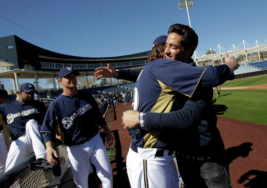 """FILE - IN this Feb. 24, 2012 file photo, Milwaukee Brewers' Ryan Braun, right, gets a hug from teammate John Axford after a news conference at spring training baseball, in Phoenix. Braun stood on a spring training field and proclaimed he was innocent of using banned testosterone. """"I would bet my life,"""" he said back then, """"that this substance never entered my body at any point."""" Seventeen months later, he accepted a 65-game suspension from baseball and admitted, """"I am not perfect. (AP Photo/Jae C. Hong, File) / AP"""