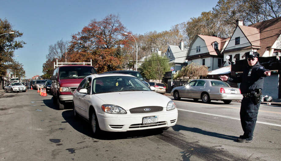 Police direct cars in line to gas station pumps on Friday, Nov. 9, 2012 in Brooklyn, N.Y. Police were at gas stations to enforce a new gasoline rationing plan that lets motorists fill up every other day that started in New York on Friday morning. (AP Photo/Bebeto Matthews) / AP