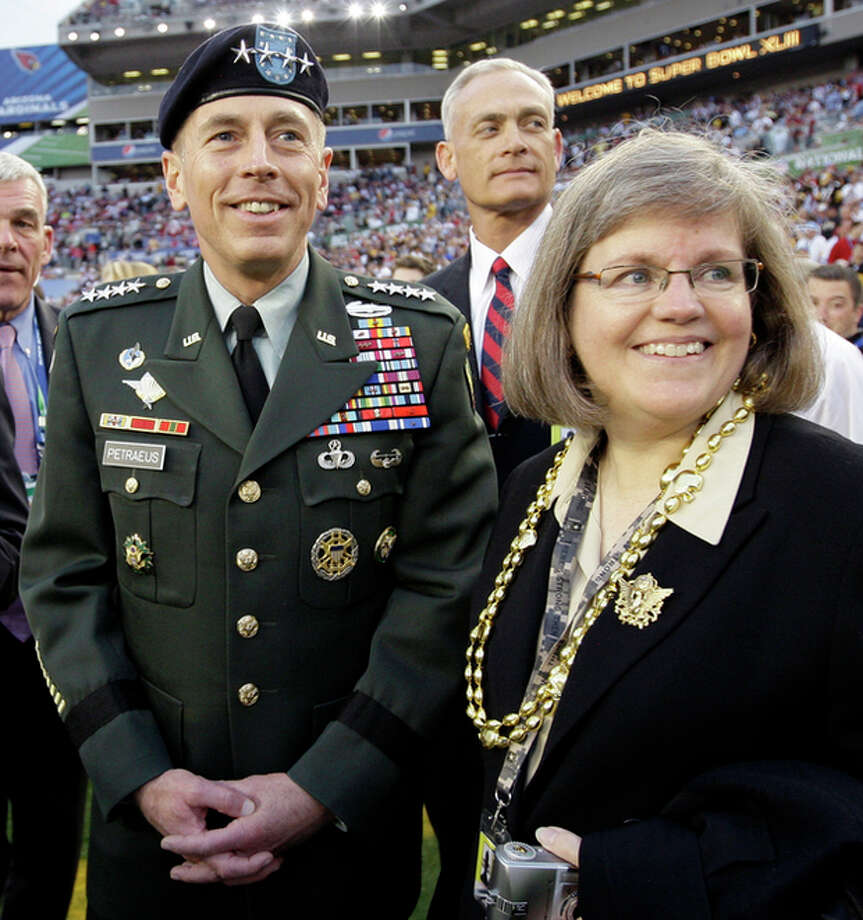 FILE - In this Feb. 1, 2009 file photo, Gen. David Petraeus, commander U.S. Central Command, left, stands with his wife Holly before the NFL Super Bowl XLIII football game between the Arizona Cardinals and the Pittsburgh Steelers in Tampa, Fla. Gen. Petraeus, the retired four-star general who led the U.S. military campaigns in Iraq and Afghanistan, resigned Friday, Nov. 9, 2012 as director of the CIA after admitting he had an extramarital affair. (AP Photo/David J. Phillip, File) / AP