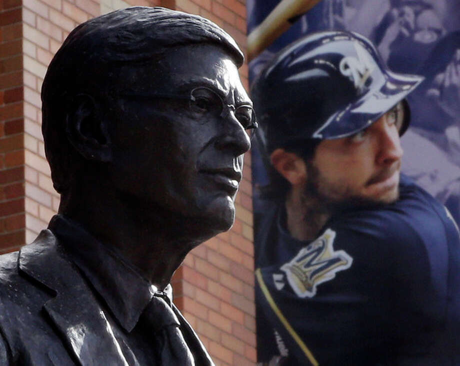 A statue of Major League Baseball Commissioner Bud Selig is displayed outside of Miller Park where a banner showing suspended Milwaukee Brewers star Ryan Braun hangs before a baseball game between the Brewers and the San Diego Padres Tuesday, July 23, 2013, in Milwaukee. (AP Photo/Morry Gash) / AP