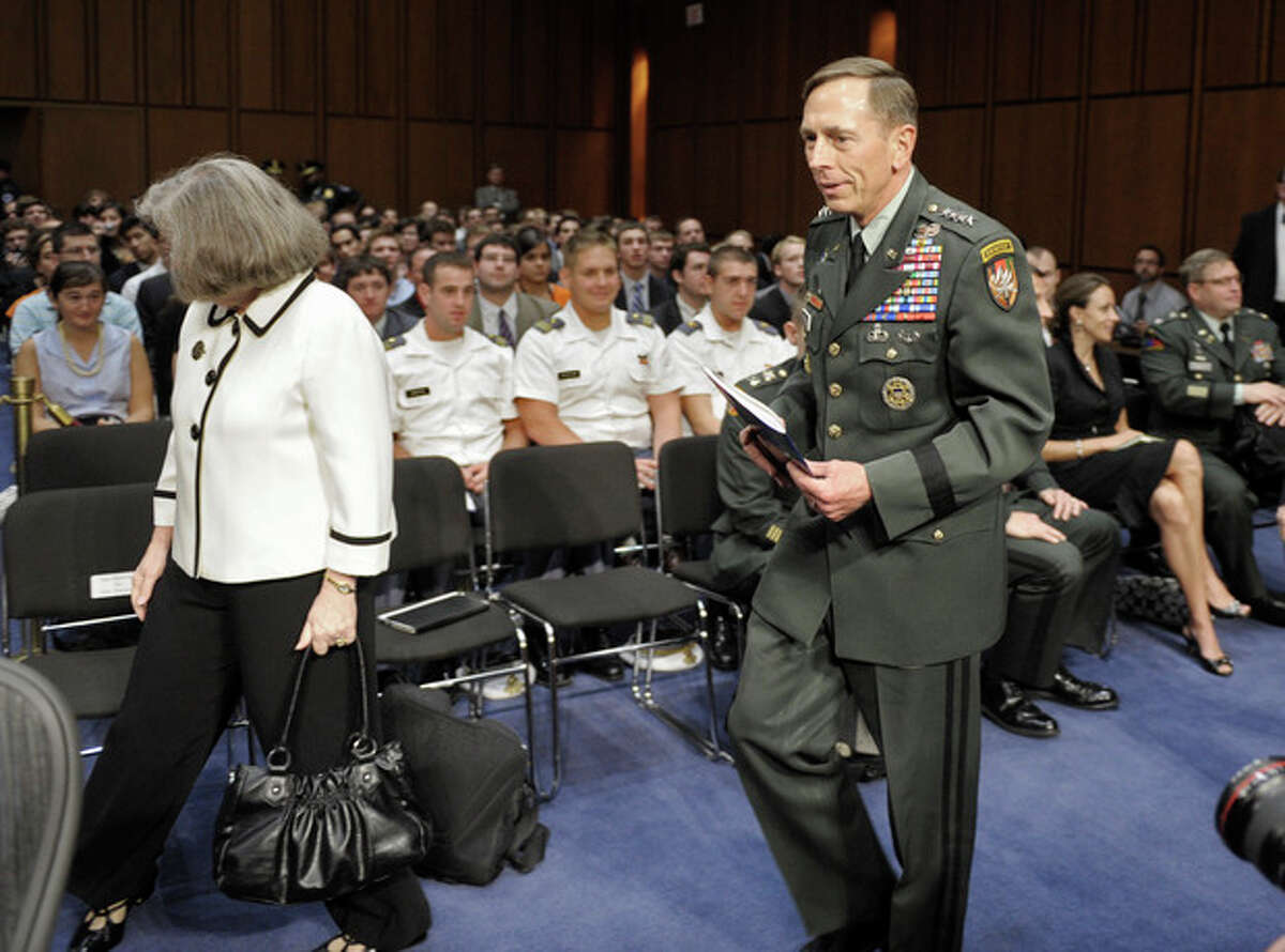 FILE - In this June 23, 2011, file photo, Gen. David Petraeus, center, walks with his wife Holly, left, past a seated Paula Broadwell, rear right, as he arrives to appear before the Senate Intelligence Committee during a hearing on his nomination to be Director of the Central Intelligence Agency on Capitol Hill in Washington. Petraeus quit Nov. 9, 2012, after acknowledging an extramarital relationship. As questions arise about the extramarital affair between Petraeus and his biographer, Paula Broadwell, she has remained quiet about details of their relationship. However, information has emerged about Jill Kelley, the woman who received the emails from Broadwell that led to the FBI?'s discovery of Petraeus?' indiscretion. (AP Photo/Cliff Owen, File)