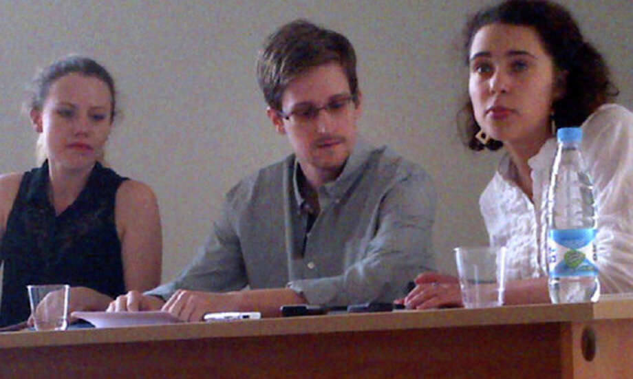FILE - In this image provided by Human Rights Watch, NSA leaker Edward Snowden, center, attends a news conference at Moscow's Sheremetyevo Airport with Sarah Harrison of WikiLeaks, left, Friday, July 12, 2013. Russian state news agency said Wednesday, July 24, 2013 that US leaker Edward Snowden has been granted a document that allows him to leave the transit zone of a Moscow airport and enter Russia. Snowden has applied for temporary asylum in Rusia last week after his attempts to leave the airport were thwarted. The United States wants him sent home to face prosecution for espionage. (AP Photo/Human Rights Watch, Tanya Lokshina) / Human Rights Watch