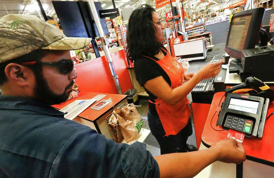 Robert Montanez, 39, left, inserts his debit card, equipped with an EMV chip, into an EMV reader while making a purchase at a Home Depot store in Burbank, Calif., on Sept. 23, 2015. Photo: Mel Melcon /McClatchy-Tribune News Service / Los Angeles Times