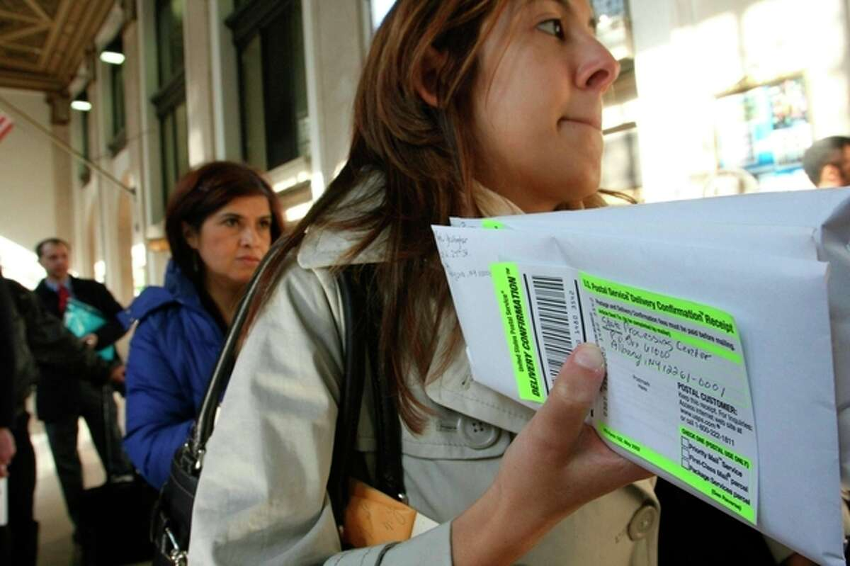 """FILE - In this April, 15, 2008, file photo, Dana Pinero, of New York, foreground, waits in line to mail tax returns for both herself and her boyfriend at the James A. Farley Main Post Office in New York. The package of tax increases and spending cuts known as the ?""""fiscal cliff?"""" takes effect on January 1, 2013, unless Congress passes a budget deal by then. The economy would be hit so hard that it would likely sink into recession in the first half of 2013, economists say. (AP Photo/Tina Fineberg, File)"""