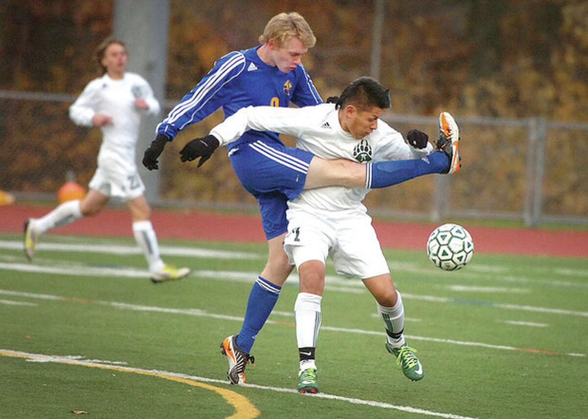 Hour Photo Alex von Kleydorff Newtown's Charles Helgren, left, and Alejandro Rivera of Norwalk get tangled up as they try to play the ball during Tuesday's Class LL state tournament quarterfinal contest at Norwalk's Testa Field. Top-seeded Norwalk overcame an early deficit to post a 2-1 victory and advance to the semifinals.