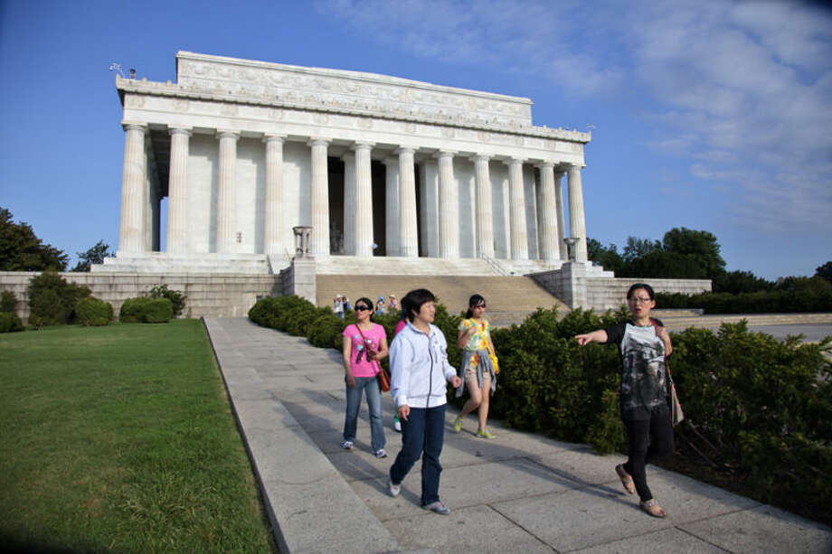 Visitors leave the Lincoln Memorial in Washington, Friday, July 26, 2013, after the U.S. Park Police closed it off after someone splattered green paint on the statue and the floor area of the memorial. Police say the apparent vandalism was discovered early Friday morning. No words, letters or symbols were visible in the paint. (AP Photo/J. Scott Applewhite)