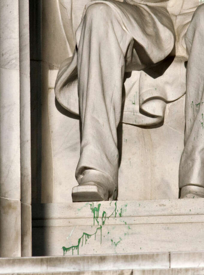 Splattered green paint is seen on the right shoe area of the Abraham Lincoln statue at the Lincoln Memorial in Washington, Friday, July 26, 2013. Police say the apparent vandalism was discovered early Friday morning. No words, letters or symbols were visible in the paint. (AP Photo/J. Scott Applewhite)