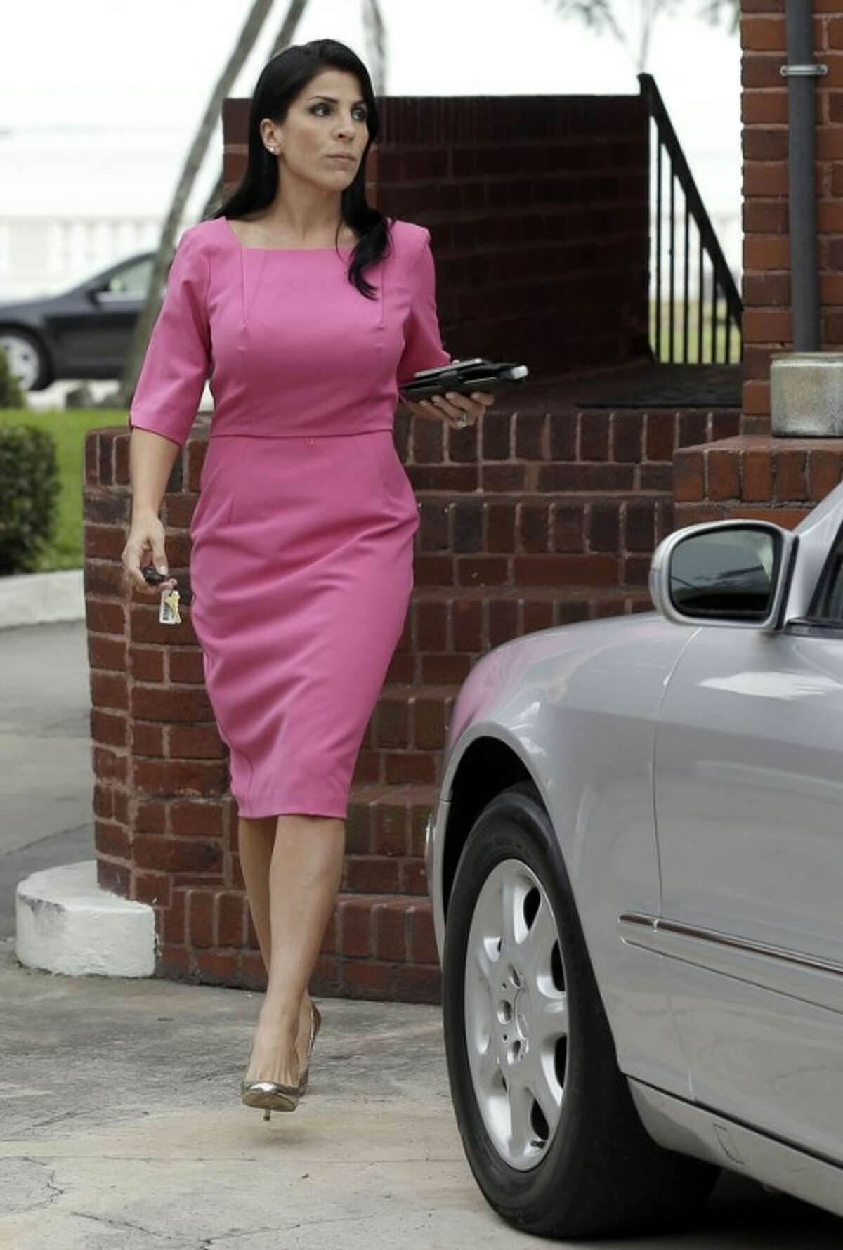 CORRECTS DATE TO 13 - Jill Kelley leaves her home Tuesday, Nov. 13, 2012 in Tampa, Fla. Kelley is identified as the woman who allegedly received harassing emails from Gen. David Petraeus' paramour, Paula Broadwell. She serves as an unpaid social liaison to MacDill Air Force Base in Tampa, where the military's Central Command and Special Operations Command are located. (AP Photo/Chris O'Meara)