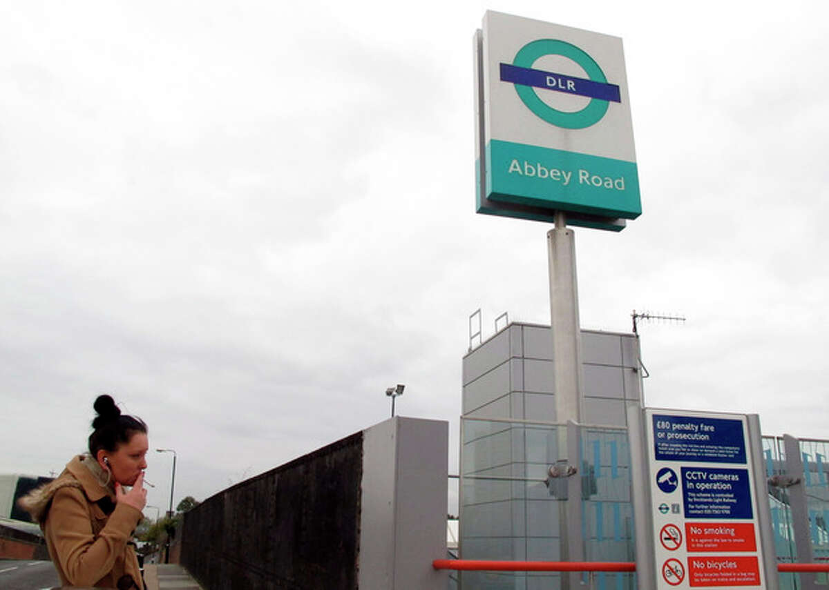 """The sign for east London's Abbey Road Station is seen against the backdrop of apartment buildings on Friday, Nov. 10, 2012. Abbey Road Station is more than nine miles from the striped crosswalk made famous by the Beatles album ?""""Abbey Road,?"""" but this drab transit hub keeps drawing confused fans of the Fab Four into unwanted jaunts through a gritty, industrial area of east London. (AP Photo/Raphael Satter)"""