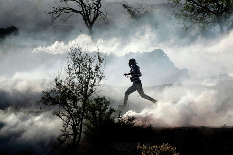 A Palestinian demonstrator runs through a cloud of tear gas during clashes against Israel's operations in Gaza Strip, outside Ofer, an Israeli military prison near the West Bank city of Ramallah, Thursday, Nov. 15, 2012. Meanwhile, Palestinian President Mahmoud Abbas cut short a trip to Europe to deal with the crisis. (AP Photo/Majdi Mohammed) / AP