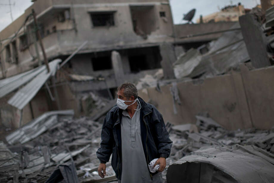 A Palestinian man walks among debris after an Israeli airstrike at Hamas Prime Minister Ismail Haniyeh's office, right, in Gaza City, Saturday, Nov. 17, 2012. Israel bombarded the Hamas-ruled Gaza Strip with more than 180 airstrikes early Saturday, widening a blistering assault on militant operations to target government and police compounds and a vast network of smuggling tunnels. (AP Photo/Bernat Armangue) / AP2011