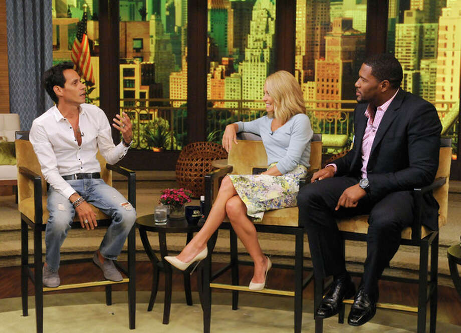"""This image released by Disney-ABC Domestic Television shows Marc Anthony, left, with co-hosts Kelly Ripa, center, and Michael Strahan on """"Live with Kelly and Michael,"""" Thursday, July 18, 2013, in New York. Marc Anthony touted his roots on """"Live with Kelly and Michael"""" on Thursday after some people criticized his selection to sing """"God Bless America"""" at this week's major league baseball All-Star Game, held in New York. The Grammy-winning salsa star said that he heard people were questioning why a foreign-born person was singing the patriotic song. Anthony said he was born in New York and added: """"You can't get more New York than me."""" (AP Photo/Disney-ABC Domestic Television, Jeff Neira) / Disney-ABC Domestic Television"""