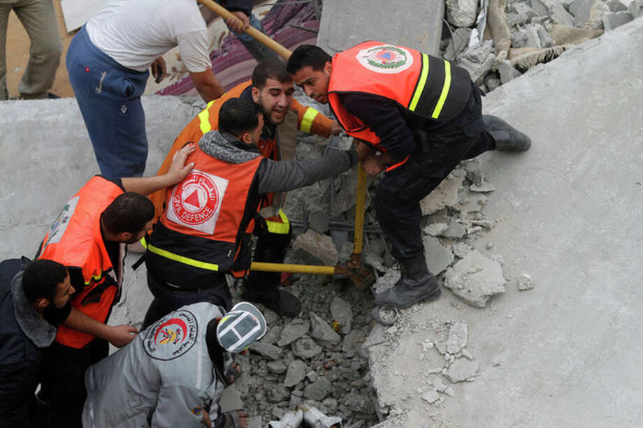 Palestinian firefighters work at the scene of an Israeli air strike on a building in the Jebaliya refugee camp in the northern Gaza Strip, Saturday, Nov. 17, 2012. Israel bombarded the Hamas-ruled Gaza Strip with more than 180 airstrikes early Saturday, widening a blistering assault on militant operations to include government and police compounds, militant leaders' residences and a vast network of smuggling tunnels. (AP Photo/Hatem Moussa) / AP