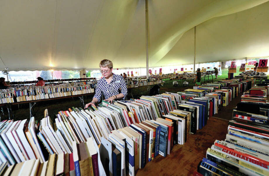 Hour photo / Erik TrautmannKelle Ruden, Community Relations Director for the Westport Public Library, sets up for the 21st annual Summer Book Sale to be held July 20-23. / (C)2013, The Hour Newspapers, all rights reserved