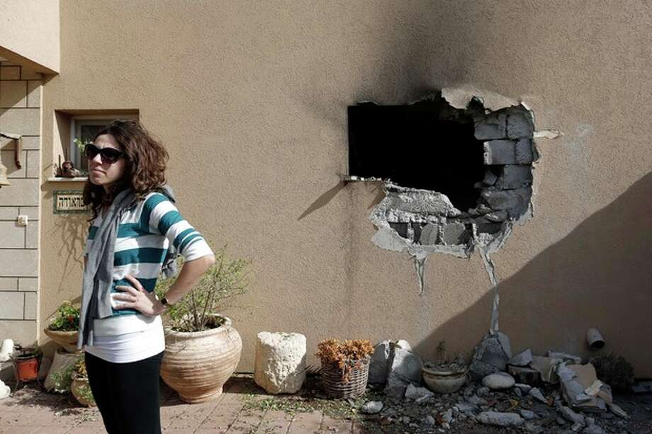 An Israeli woman stands outside a damaged house hit by a rocked fired from the Gaza Strip that hit a house near the Israel-Gaza border, Friday, Nov. 16, 2012. Fierce clashes between Israeli forces and Gaza militants are continuing for the third day.(AP Photo/Tsafrir Abayov) / AP