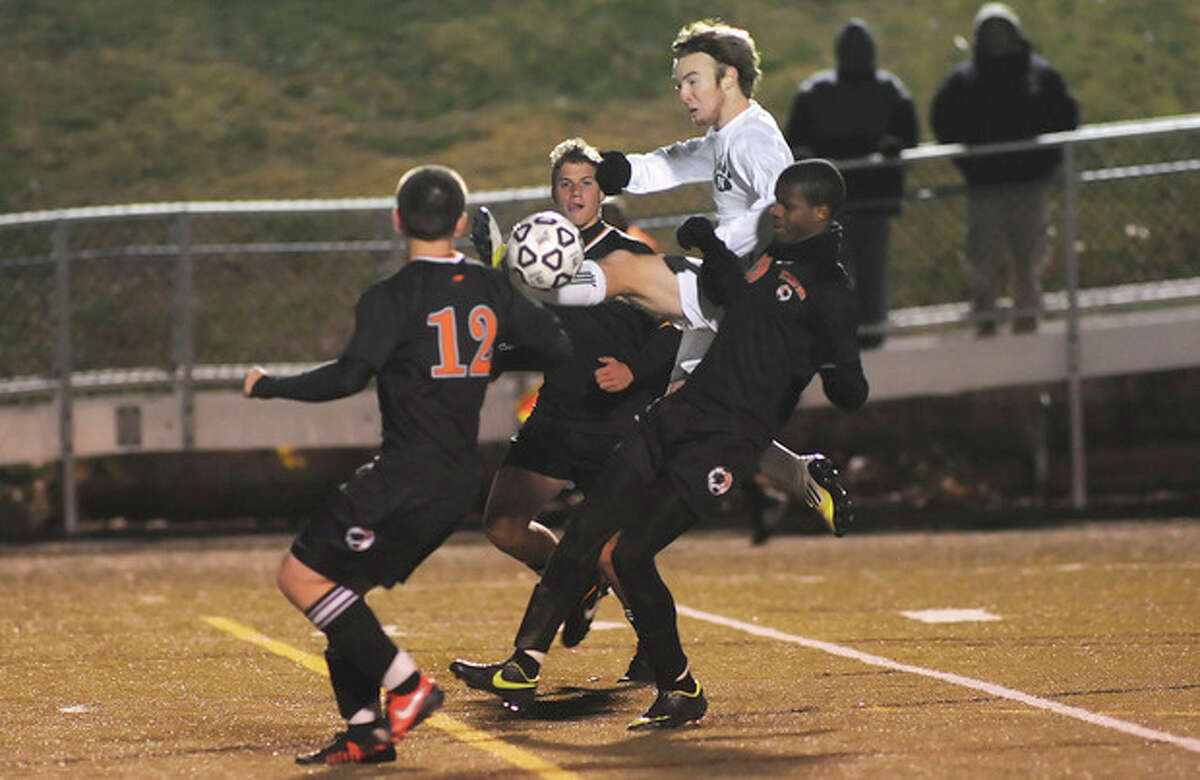Hour photo/John Nash Norwalk's Kevin Joslyn, top, goes between Stamford defenders, from left, Nazar Zhukovskyy (12), Kyle Casey and Marc Guirand during Friday's CIAC Class LL semifinal in New Canaan. Joslyn scored twice to lead the Bears to a 2-1 win.