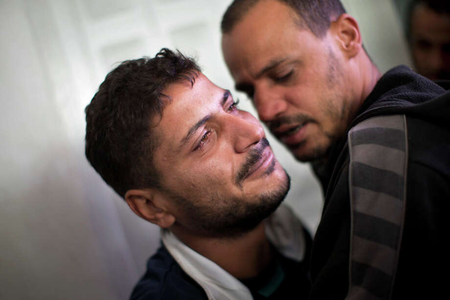 Palestinian Khaled Tafesh cries outside the morgue of Shifa Hospital before taking the dead body of his 10-month-old infant in Gaza City, Friday, Nov. 16, 2012. According to hospital reports, Haneen Tafesh died from wounds of an earlier Israeli strike. (AP Photo/Bernat Armangue) / AP
