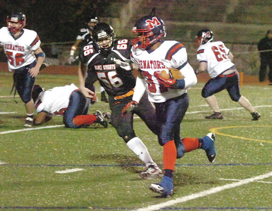 Hour photo/Alex von KleydorffBrien McMahon's Kyle Jordan, right, tries to beat a Stamford defender to the corner during Friday night's game in Stamford. Jordan ran for 283 yards and four TDs in McMahon's 47-26 victory. / 2012 The Hour Newspapers