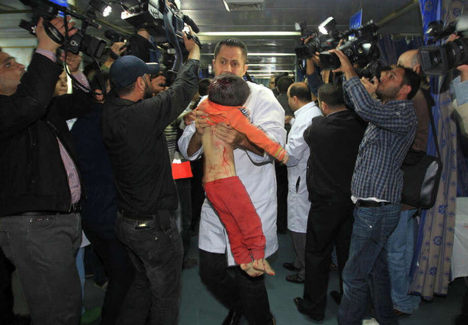 A medic carries the body of a Palestinian boy, who they claim was killed in an Israeli strike on Gaza City, to an event in which media were invited to cover the visit of Hamas Prime Minister Ismail Haniyeh and Egyptian Prime Minister Hesham Kandil at Shifa hospital in Gaza City, Friday, Nov. 16, 2012. Neighbors said the boy was killed in a blast around 8:30 a.m. Friday, around the time Kandil was entering the territory. Israel, which ordinarily confirms strikes, vociferously denied carrying out any form of attack in the area since the previous night. (AP Photo/Mahmud Hams, Pool) / Pool AFP