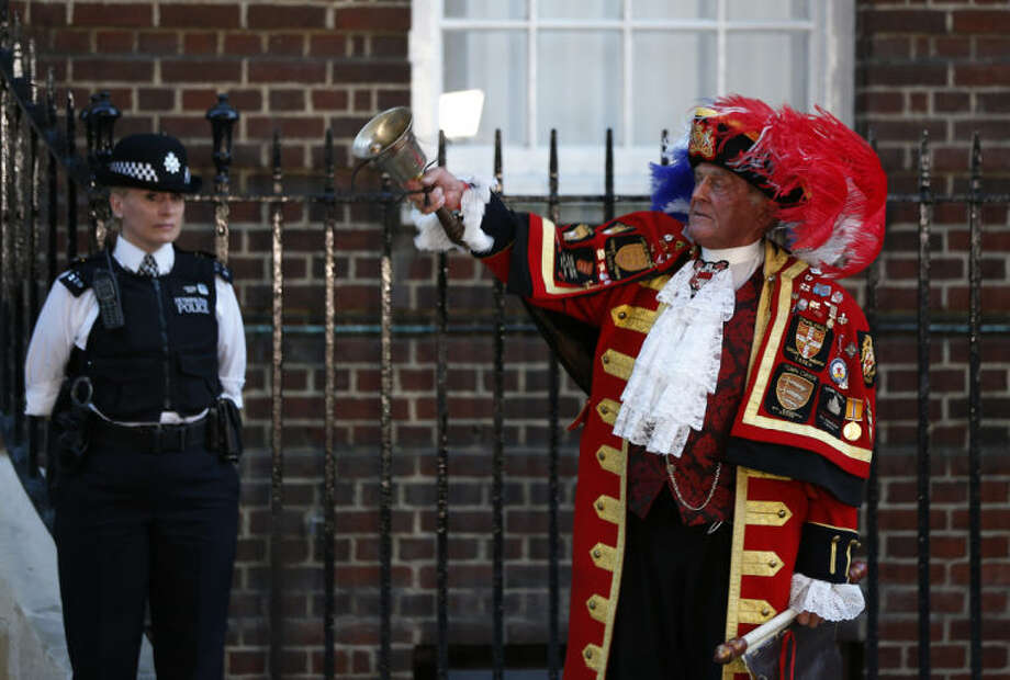 Tony Appleton, a town crier, rings his bell as he announces the birth of the royal baby, outside St. Mary's Hospital exclusive Lindo Wing in London, Monday, July 22, 2013. Palace officials say Prince William's wife Kate has given birth to a baby boy. The baby was born at 4:24 p.m. and weighs 8 pounds 6 ounces. The infant will become third in line for the British throne after Prince Charles and William. (AP Photo/Lefteris Pitarakis)